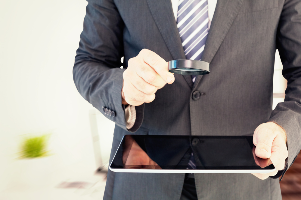 Businessman looking at tablet with magnifying glass against laptop on desk with glasses and notepad
