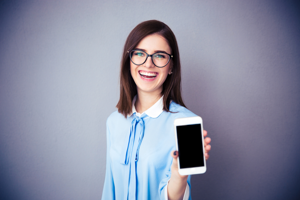 Laughing businesswoman showing blank smartphone screen over gray background. Wearing in blue shirt and glasses. Looking at camera.