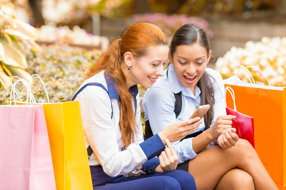 Closeup portrait two surprised girls looking at cell phone discussing latest gossip news. Young shopping women reading news on smartphone, sitting in park on a bench. Face expression body language