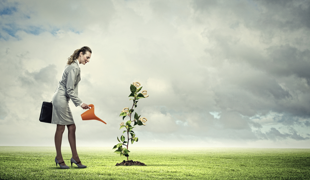 Image of business woman watering money tree. Currency concept