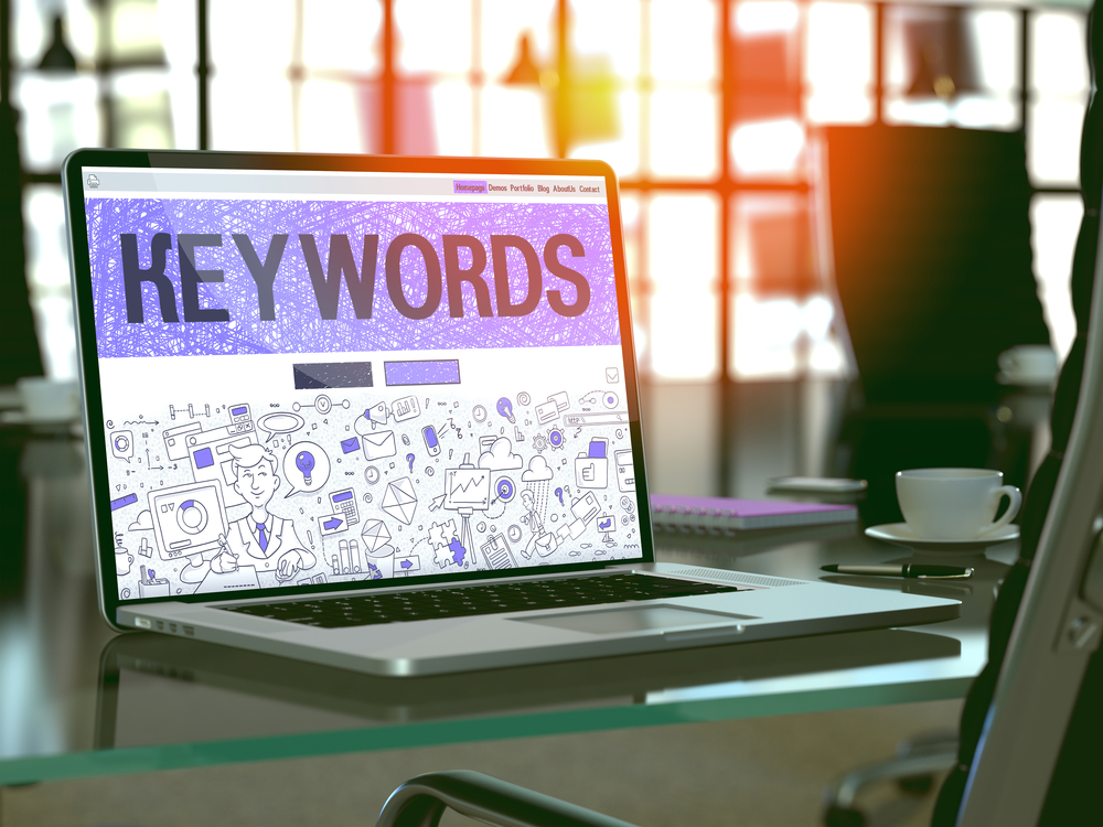 Keywords - Closeup Landing Page in Doodle Design Style on Laptop Screen. On Background of Comfortable Working Place in Modern Office. Toned, Blurred Image. 3D Render.