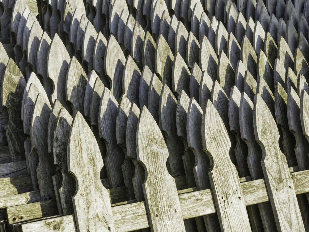 Pattern of weathered wooden fence posts, shaped like arrowheads, near sunset