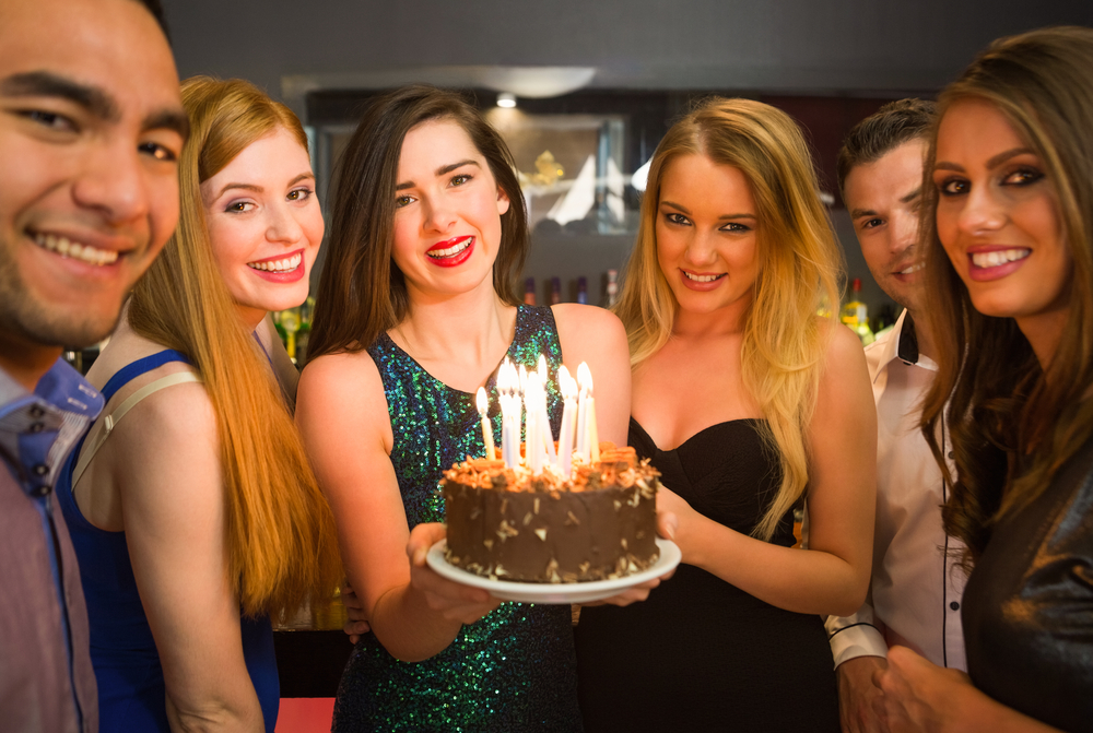 Happy friends celebrating brithday one holding birthday cake looking at camera in a nightclub-1