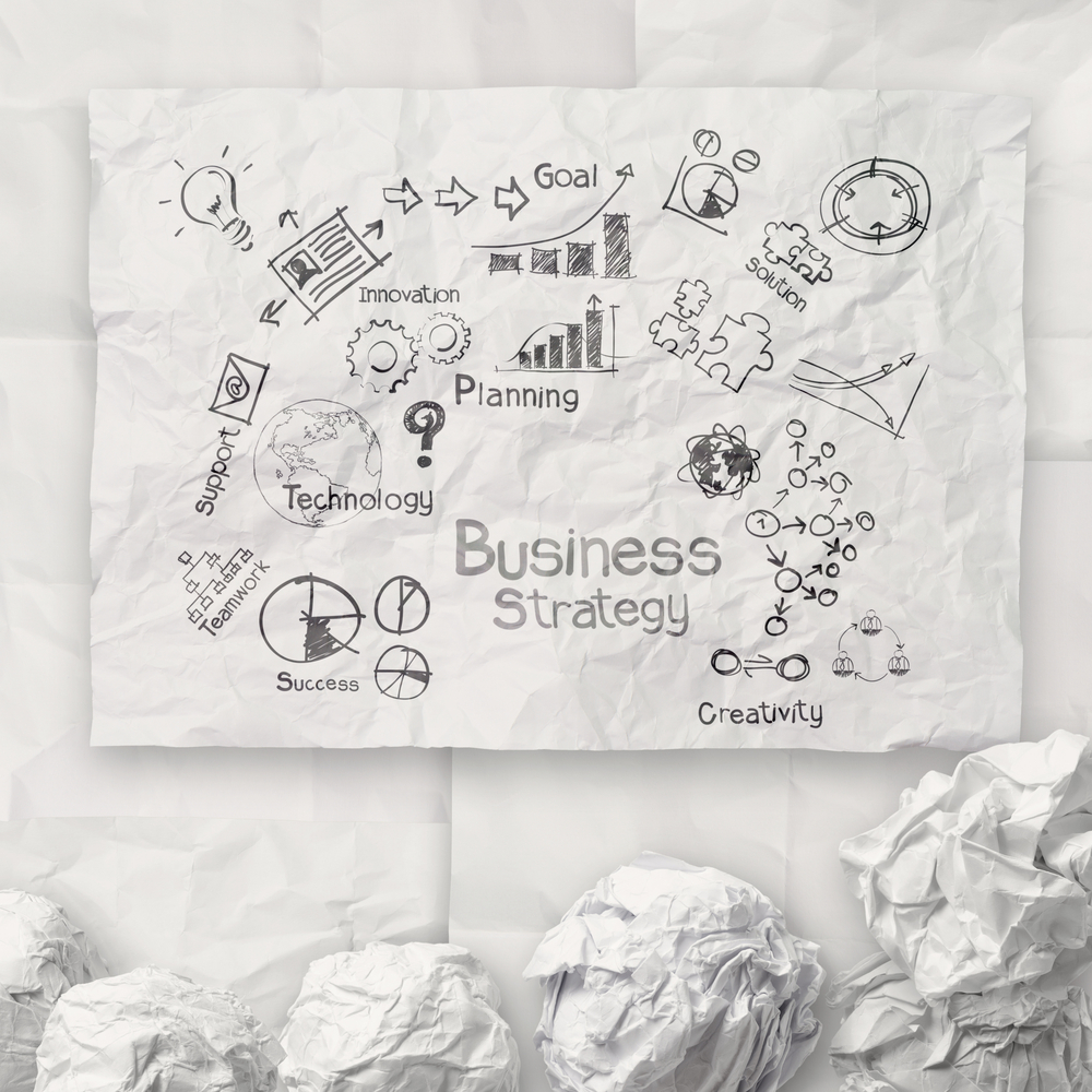hand drawing creative business strategy on crumpled paper background as concept